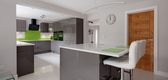 Contemporary fitted kitchen in striking lime green, grey and white colour scheme with built in appliances, white granite counter tops dual ovens island breakfast bar and hob